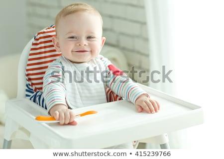 Genç çocuk yeme yüksek sandalye kırmızı Stok fotoğraf © gewoldi