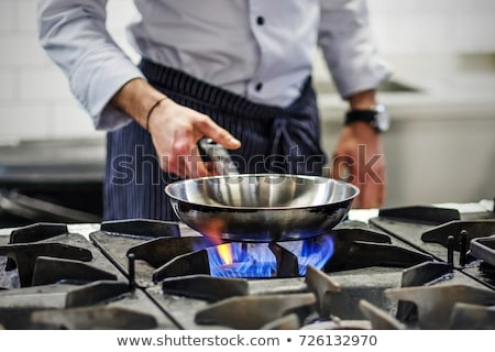 Hand and frying pan with gas-stove Stock photo © ozaiachin