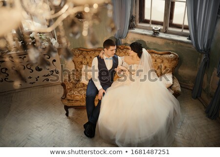 Bride sitting on couch, groom looks out window Stock photo © pzaxe