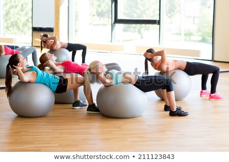 Fit young woman with happy smile balancing on exercise ball stock photo © darrinhenry