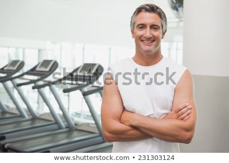 Fit man smiling at camera beside treadmills Stock photo © wavebreak_media