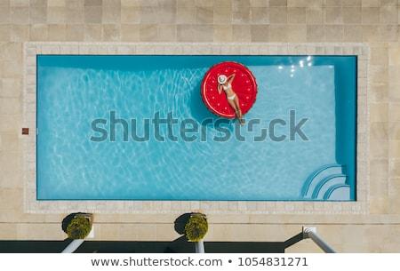 Mujer tomar el sol colchón piscina retrato mujer hermosa Foto stock © deandrobot