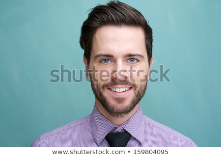 close up of cheerul attractive bearded young male with headphones stock photo © deandrobot