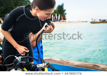 Woman with oxygen flasks for scuba diving in tropic sea Stock photo © Kzenon