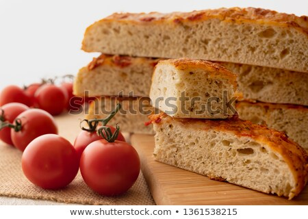 Focaccia with tomato and onions on a wooden board on a white bac stock photo © d_duda
