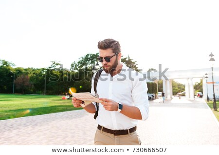 серьезный бородатый человека Солнцезащитные очки чтение газета Сток-фото © deandrobot