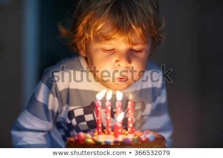 Boy blowing out birthday candle Stock photo © IS2