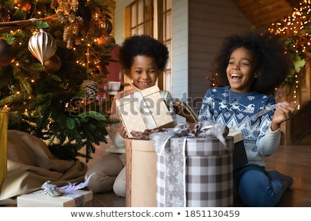 Stock photo: Family at Christmas day unwrapping presents under the tree