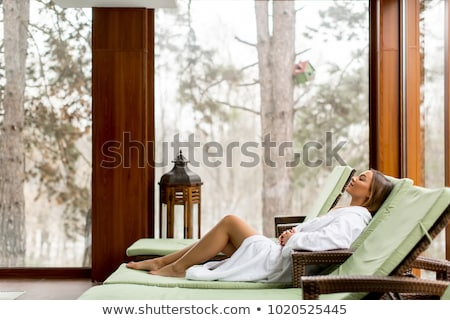 Stock photo: Pretty young women relaxing on the deckchair by the swimming poo