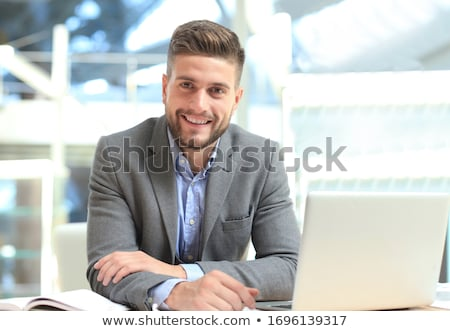 Image of successful businessman 30s in suit smiling and holding  stock photo © deandrobot
