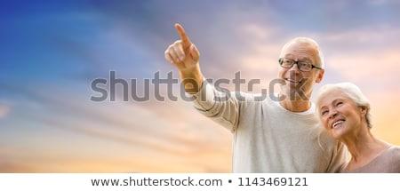 happy senior couple holding hands over evening sky Stock photo © dolgachov