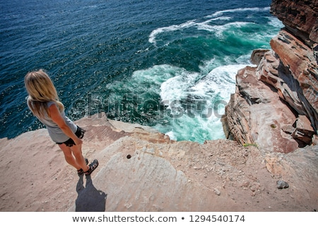 Female takes in the ocean views from cliff top ledge on the coast Stok fotoğraf © lovleah