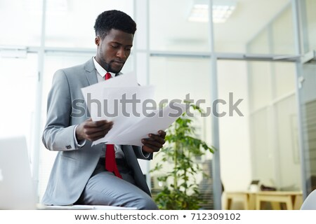elegant accountant or broker looking through financial papers stock photo © pressmaster