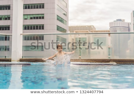 Boy jumping into the pool among the skyscrapers and the big city. Relax in the big city. Rest from s Stock photo © galitskaya