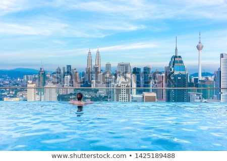 Young woman in outdoor swimming pool with city view in blue sky VERTICAL FORMAT for Instagram mobile Stock photo © galitskaya
