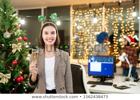 Cheerful female office manager with flute of champagne standing by xmas tree Stock photo © pressmaster