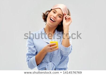 woman in pajama and sleeping mask with juice Stock photo © dolgachov