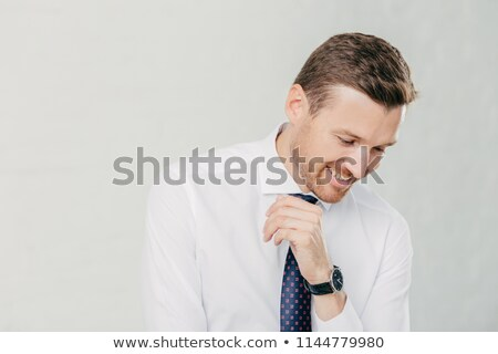 Positive unshaven man looks happily down, dressed in elegant clothes, stands against white backgroun Stock photo © vkstudio