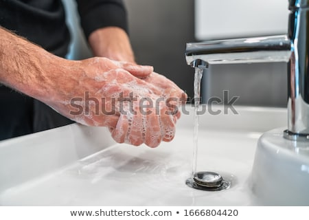 Corona virus travel prevention man showing hand hygiene washing hands with soap in hot water for cor Stock photo © benzoix