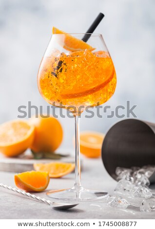 Glass of aperol spritz summer cocktail with oranges bar spoon and cocktail shaker on light backgroun Stock photo © DenisMArt