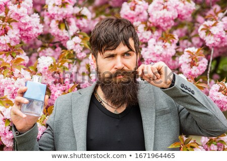 Adult male holding a bottle of aftershave or men's fragrance Stock photo © lovleah
