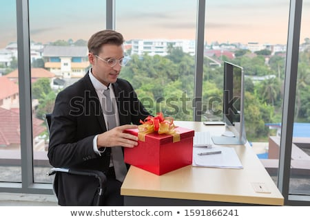 Smiling businessman holding gift box with red ribbon Stock photo © HASLOO