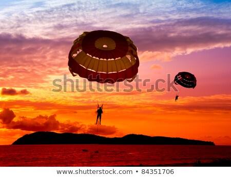 Silhouette of a parasailor at sunse Stock photo © natalinka