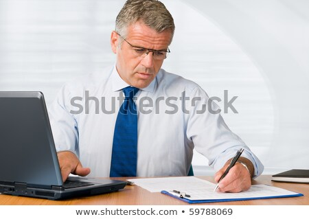 smiling businessman examining document on clipboard stock photo © andreypopov