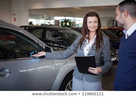 businesswoman presenting something on clipboard stock photo © deandrobot