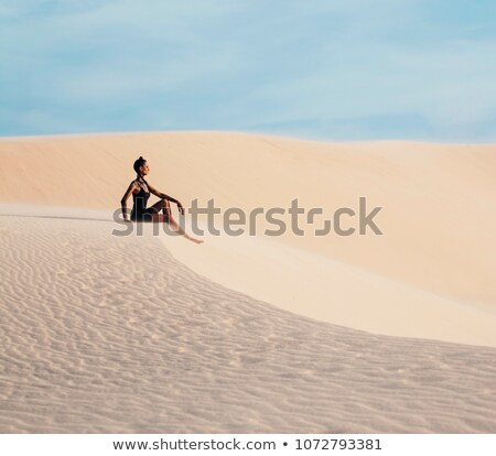 young pretty woman in white sand dunes like a goddes of darkness Stock photo © iordani