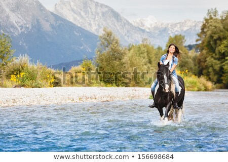 young woman crossing a river by horse stock photo © monkey_business