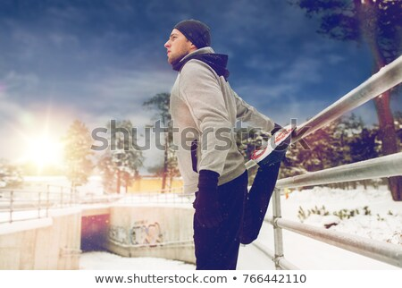 sports man stretching leg at fence in winter stock photo © dolgachov