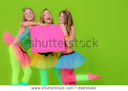 fashion girls in neon clothing holding blank pink billboard stock photo © godfer