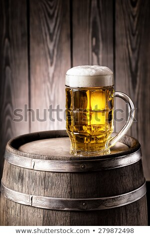wooden barrel and full wooden beer mug with thick white foam stock photo © orensila