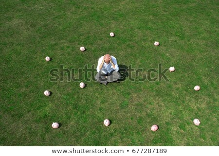 man sitting amongst piggy banks stock photo © is2