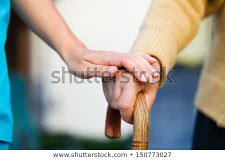 Elderly woman holding a walking stick Stock photo © IS2