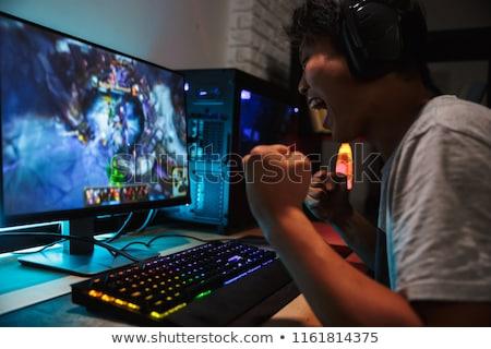 férfi · játszik · játék · asztali · számítógép · hátsó · nézet · fiatalember - stock fotó © deandrobot