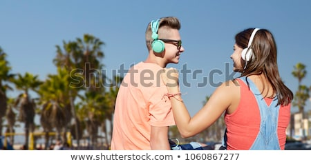 teenage couple with headphones at venice beach stock photo © dolgachov