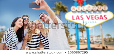 friends in party clothes hugging at las vegas Stock photo © dolgachov