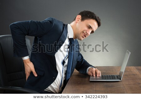Man suffering from backache while sitting at computer desk in office Stock photo © Lopolo