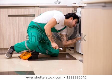 Young contractor repairing washing machine in kitchen Stock photo © Elnur