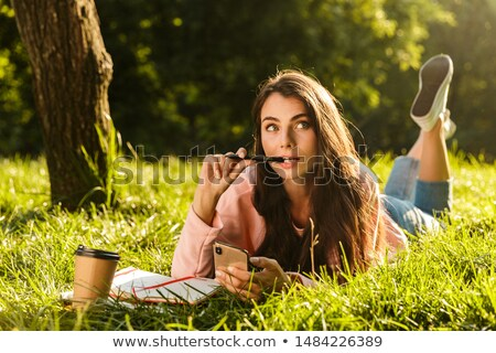 Peinzend jong meisje leggen gras park met behulp van laptop Stockfoto © deandrobot