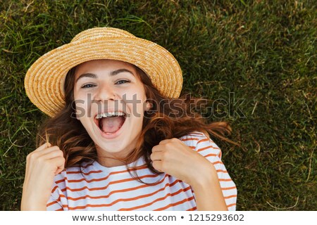 Top view of a cheery young girl in summer hat Stock photo © deandrobot