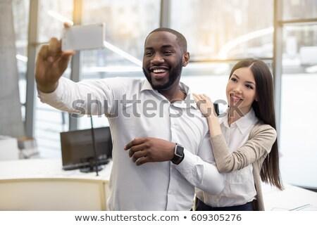 служащий · смартфон · случайный · сидят · столе · улыбаясь - Сток-фото © deandrobot