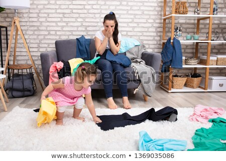 Shocked Mother Looking At Her Daughter Spreading Clothes Stock photo © AndreyPopov