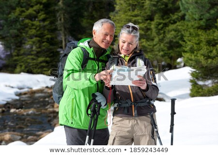 Senior active husband and wife with backpacks and map during trekking trip Stock photo © pressmaster