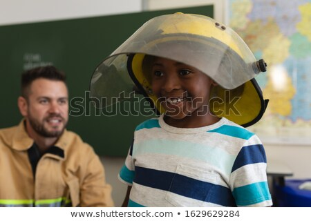 Front view of a happy black schoolboy wearing fire helmet and a smiling firefight behind him in clas Stock photo © wavebreak_media