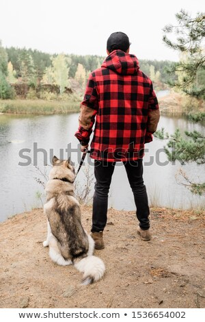 Young man in casualwear holding leash of his pet while both looking at lake Stock photo © pressmaster