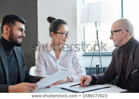 Mature agent consulting two intercultural business partners during negotiation Stock photo © pressmaster