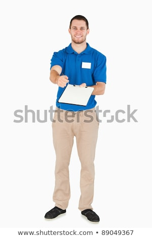 Smiling young salesman asking for signature against a white background Stock photo © wavebreak_media